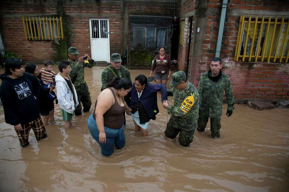Soldiers help a woman to leave her flooded house to take her to a shelter in Zoatlan, Nayarit state, some 150 km northwest of Guadalajara,  Mexico, Saturday, Oct. 24, 2015. Hurricane Patricia made landfall Friday on a sparsely populated stretch of Mexico's Pacific coast as a Category 5 storm, avoiding direct hits on the resort city of Puerto Vallarta and major port city of Manzanillo as it weakened to tropical storm force while dumping torrential rains that authorities warned could cause deadly floods and mudslides. (AP Photo/Eduardo Verdugo) Photo: Eduardo Verdugo, STF / Associated Press / AP