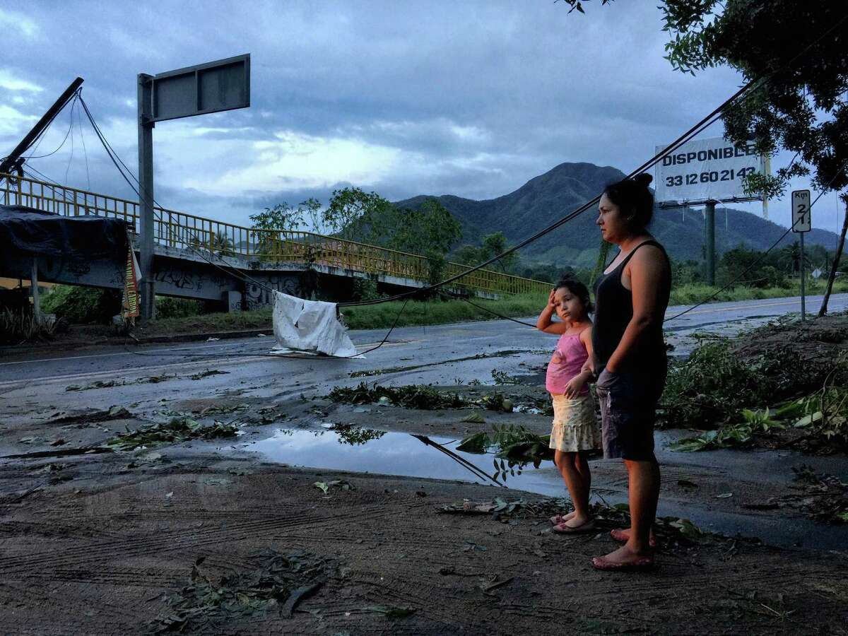 Rosario Ruiz Figueroa and her daughter Gisol Airam, 6, survey the trees and power lines downed by Hurricane Patricia near their home in El Naranjo, Mexico, Oct. 24, 2015. Patricia rapidly lost energy on Saturday as it moved inland, and while no deaths were initially reported, authorities warned of the threat of flooding and landslides. (Adriana Zehbrauskas/The New York Times)