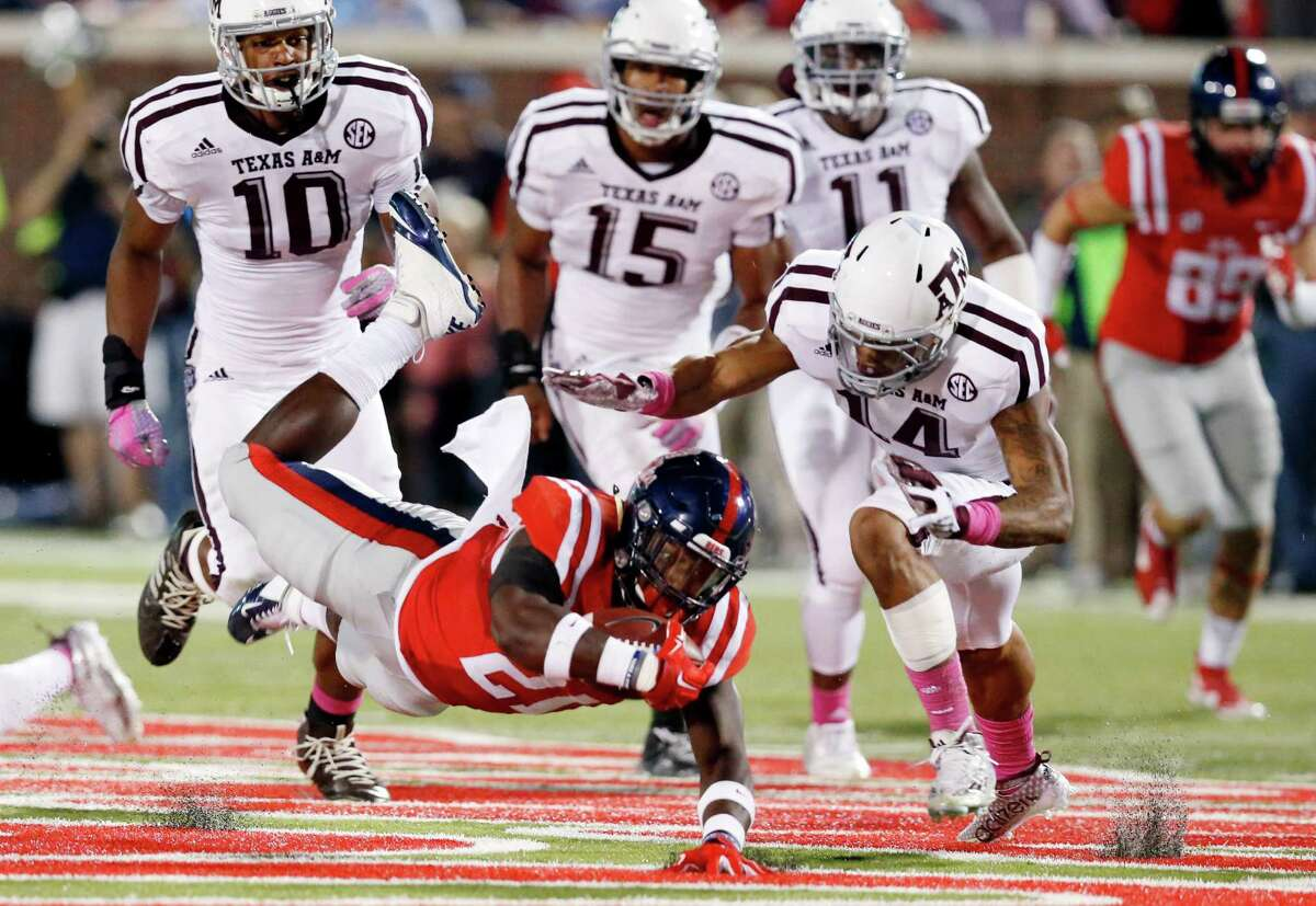 Mississippi running back Akeem Judd (21) dives for extra yards as Texas A&M defensive back Justin Evans (14) closes in to tackle during the first half of an NCAA college football game in Oxford, Miss., Saturday, Oct. 24, 2015. (AP Photo/Rogelio V. Solis)