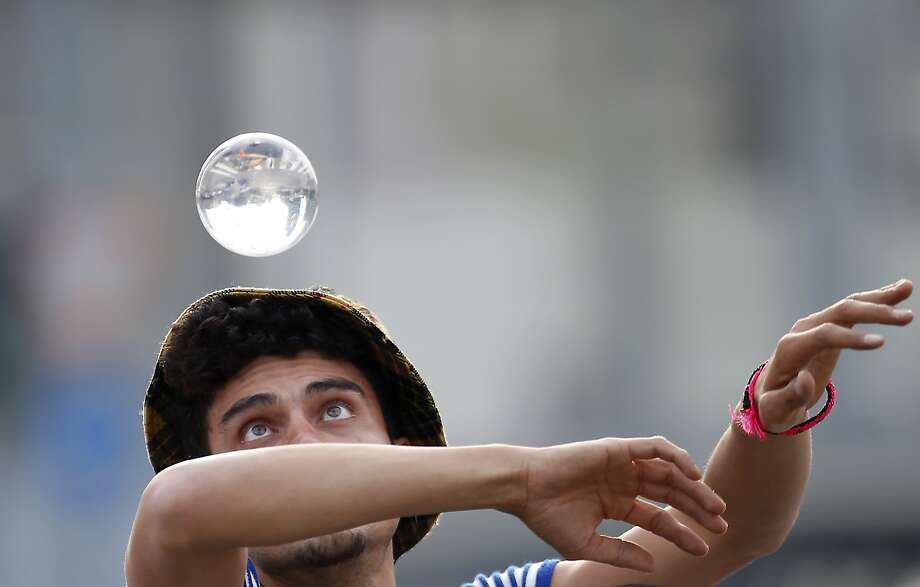 Street artist Daniele, of Chile, known as Pachama, performs with a glass ball in downtown Milan, Italy, Saturday, Oct. 24, 2015. Photo: Antonio Calanni, Associated Press