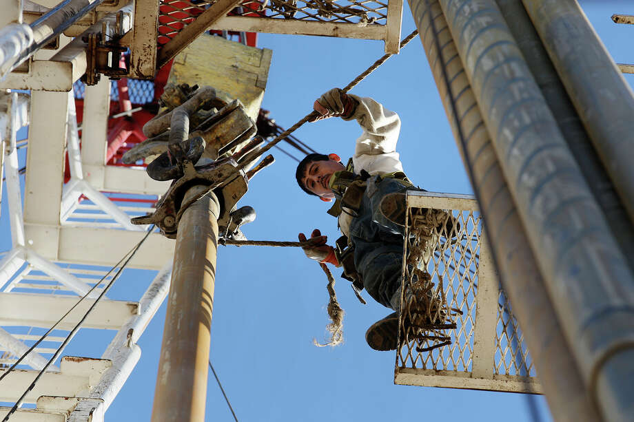Derrickman Nestor Lerma Jr. guides a drilling pipe on a rig in Atascosa County. He spent most of his life working in oil fields and died in one on May 1. Photo: Jerry Lara / San Antonio Express-News / © 2013 San Antonio Express-News