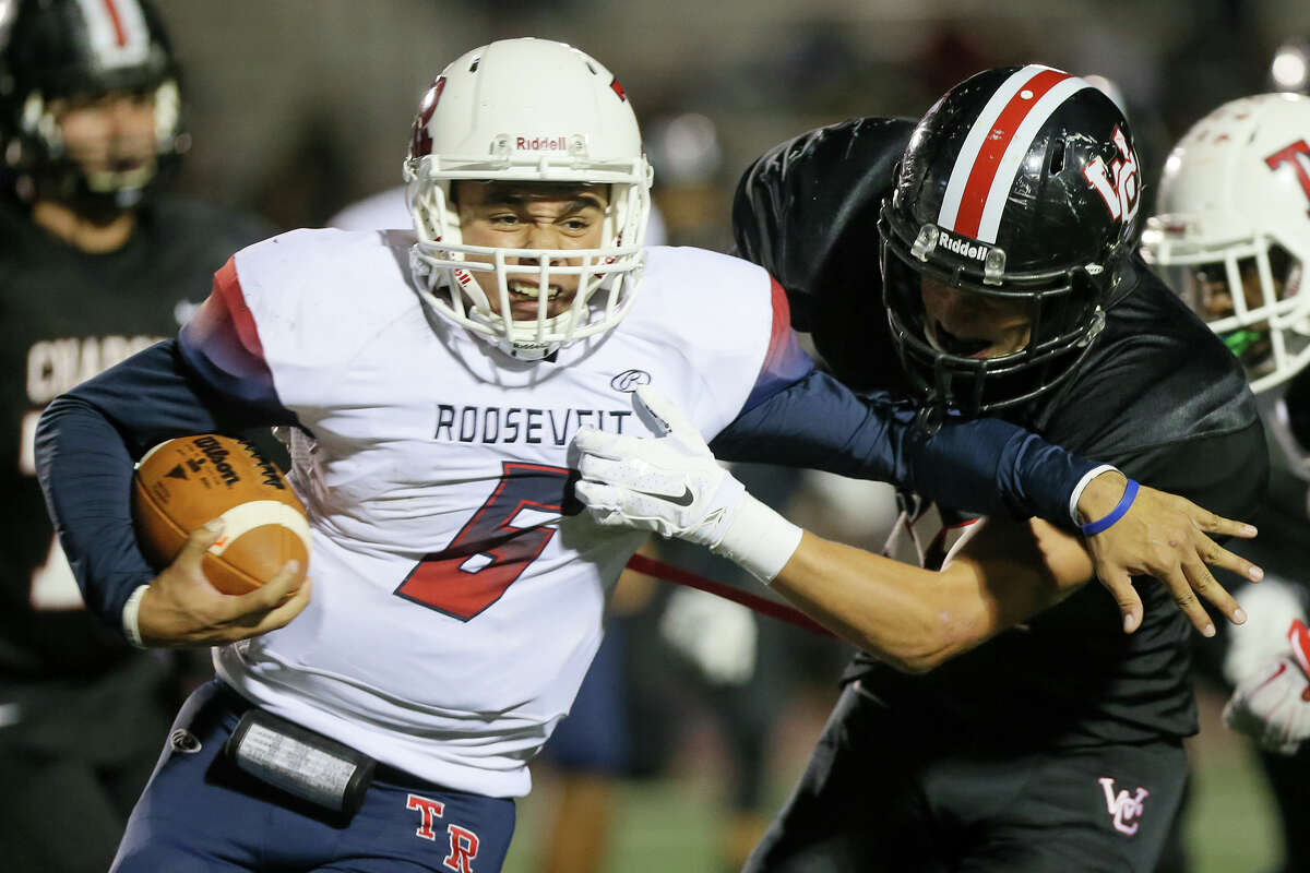 Roosevelt quarterback Bryson Carroll (left) tries to fight through a tackle by Churchill's Michael Sparkman during the second half of their District 26-6A game at Comalander Stadium on Saturday, Oct. 24, 2015. Churchill beat Roosevelt 37-14. MARVIN PFEIFFER/ mpfeiffer@express-news.net