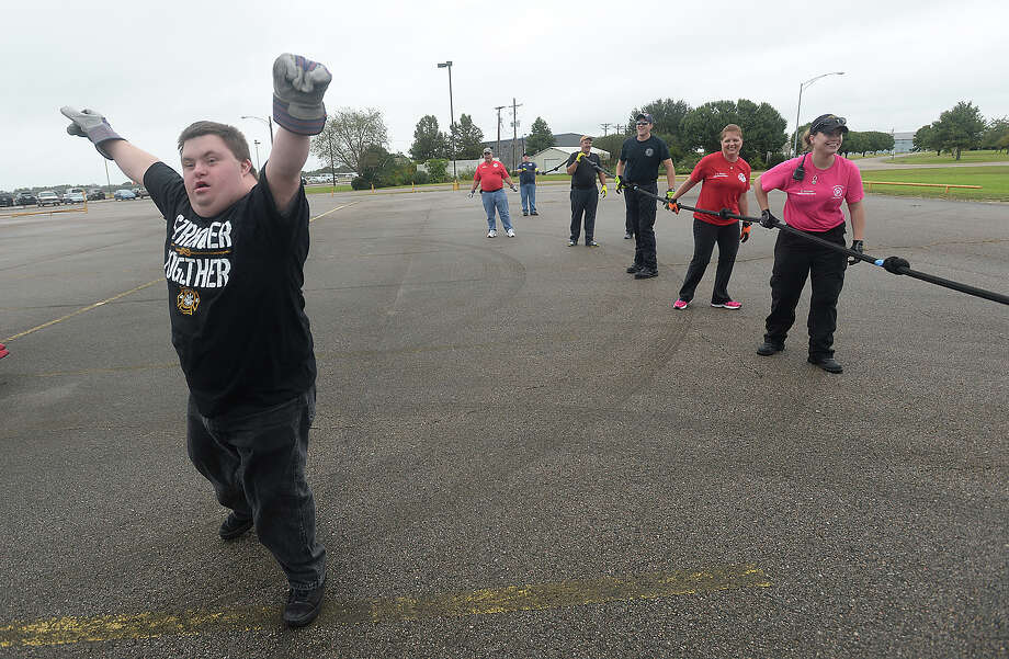 Athlete Brad Smith celebrates after he and teammates complete their run during the Fire Truck Pull Saturday morning at the Jack Brooks Regional Airport. Teams of 12 from both civilian and emergency responder groups put their collective muscles to work, playing tug-of-war with a 5,500 pound fire truck, vying to pull fastest. Proceeds from the event benefit Special Olympics Texas athletes in the Beaumont area.  Photo taken Saturday, October 24, 2015 Kim Brent/The Enterprise Photo: Kim Brent / Beaumont Enterprise