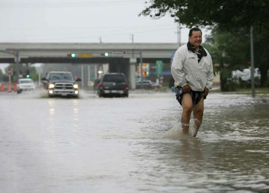 Eleazar Sanchez wades through high water on Fondren Road near the Southwest Freeway to test its depth before driving through it Sunday, Oct. 25, 2015, in Houston. Heavy rains moved into the area over night dropping four to nine inches of rain across parts of Harris County. Photo: Jon Shapley, Houston Chronicle / © 2015  Houston Chronicle