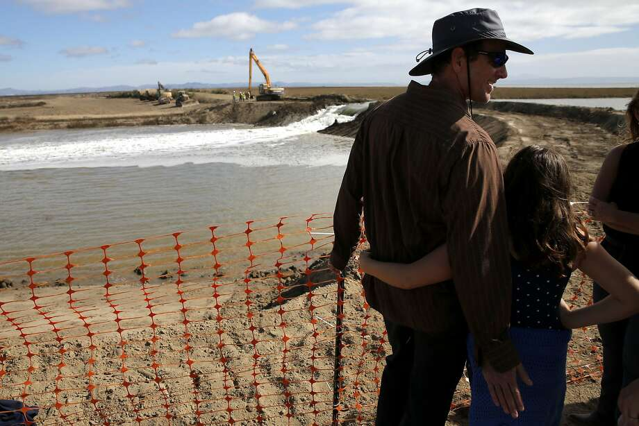 Dave Cook pats his daughter Zoey Cook, 9, while they watch water flow through the breached levee near Sonoma, California, on Sunday, Oct. 25, 2015. Photo: Connor Radnovich, The Chronicle