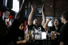 Juan Spencer center, and Clara Arroyo, right, cheer as Raiders fans watched the team's score during the game against the San Diego Chargers at The Go Sports Bar in Oakland, Calif., on Sunday, October 25, 2015. NFL Commissioner Roger Goodell's staff will arrive into Oakland Thursday to hold a public hearing on the Raiders possible move to Southern California.
