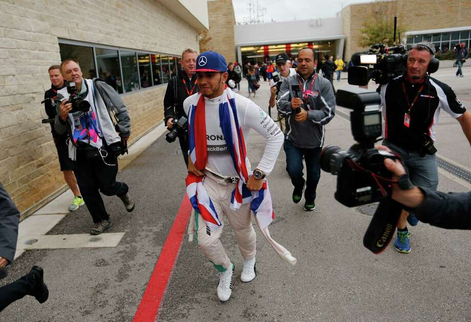 Mercedes driver Lewis Hamilton, of Britain, runs to his garage following a news conference at the Formula One U.S. Grand Prix auto race at the Circuit of the Americas, Sunday, Oct. 25, 2015, in Austin, Texas. Hamilton won the world championship after winning the race. (AP Photo/John Locher) Photo: John Locher, STF / Associated Press / AP