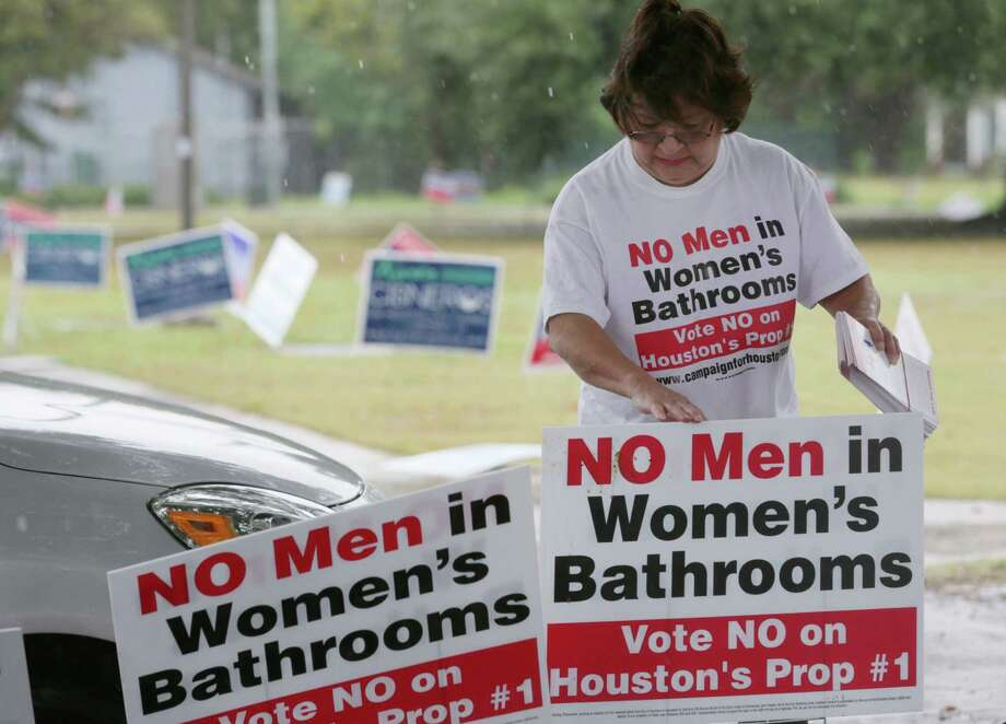 "Linda ""Granny"" Rodriguez puts up signs against Proposition 1 at the Moody Community Center Sunday, Oct. 25, 2015, in Houston. ""It's rainy, but rain or shine I'm going to be here,"" she said.  ( Jon Shapley / Houston Chronicle ) Photo: Jon Shapley, Staff / © 2015  Houston Chronicle"