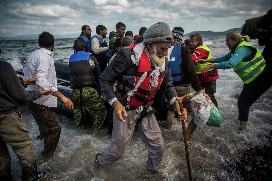 An elderly Afghan disembarks from a dinghy after arriving with other migrants and refugees from a Turkish coast to the northeastern Greek island of Lesbos. Photo: Santi Palacios /Associated Press / AP