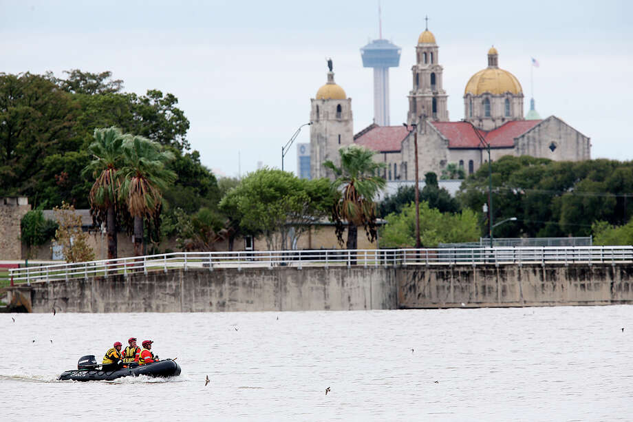 San Antonio Fire Department personnel search for a missing man at Woodlawn Lake, Sunday, Oct. 25, 2015. The man was swept away by storm waters in a drainage ditch as he went chasing after his dog early Saturday morning. Heavy rains throughout the weekend causes creeks and draining ditches to swell with water. Photo: JERRY LARA, Staff / San Antonio Express-News / © 2015 San Antonio Express-News