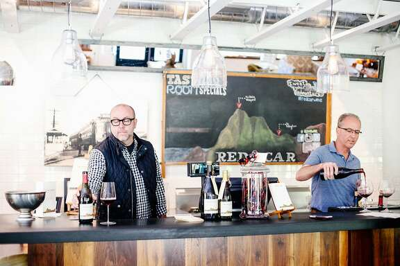 Carroll Kemp, the owner of Red Car Wine, left, and tasting room manager Rick Bidia, right, pouring wine in the tasting room in Occidental, Calif., on Wednesday, October 21, 2015.