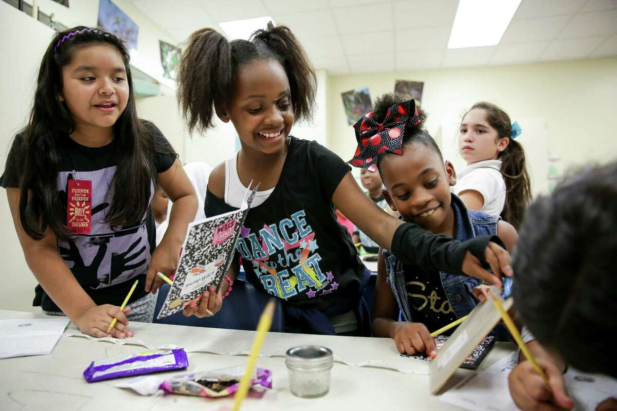 Aaliyah Williams, center, prepares to release a toy car down a clipboard covered in wax paper as Litzy Vega, left, and London Thorn, right, watch the friction experiment during Girlstart, an after-school program, last week at Heflin Elementary School in Houston.