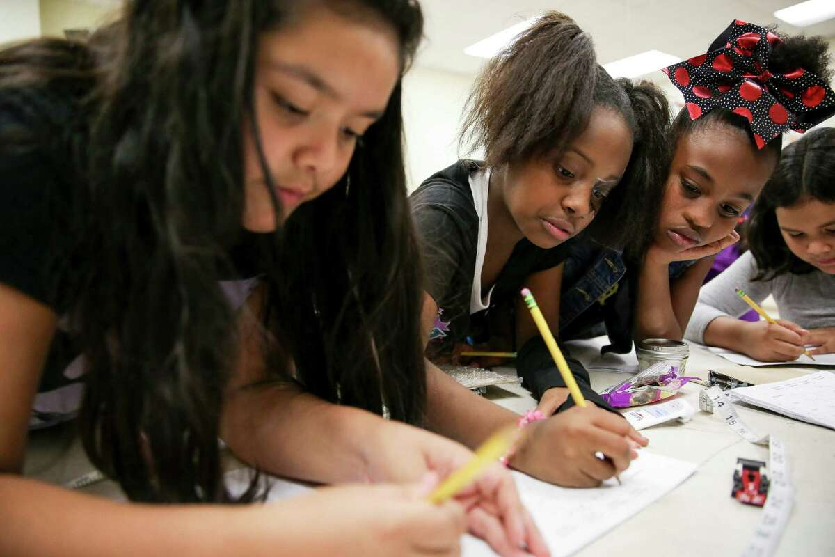Fourth- graders Litzy Vega, from left, Aaliyah Williams, and London Thorn record their results after an experiment to learn about friction during the Girlstart program last week at Heflin Elementary School in Houston.