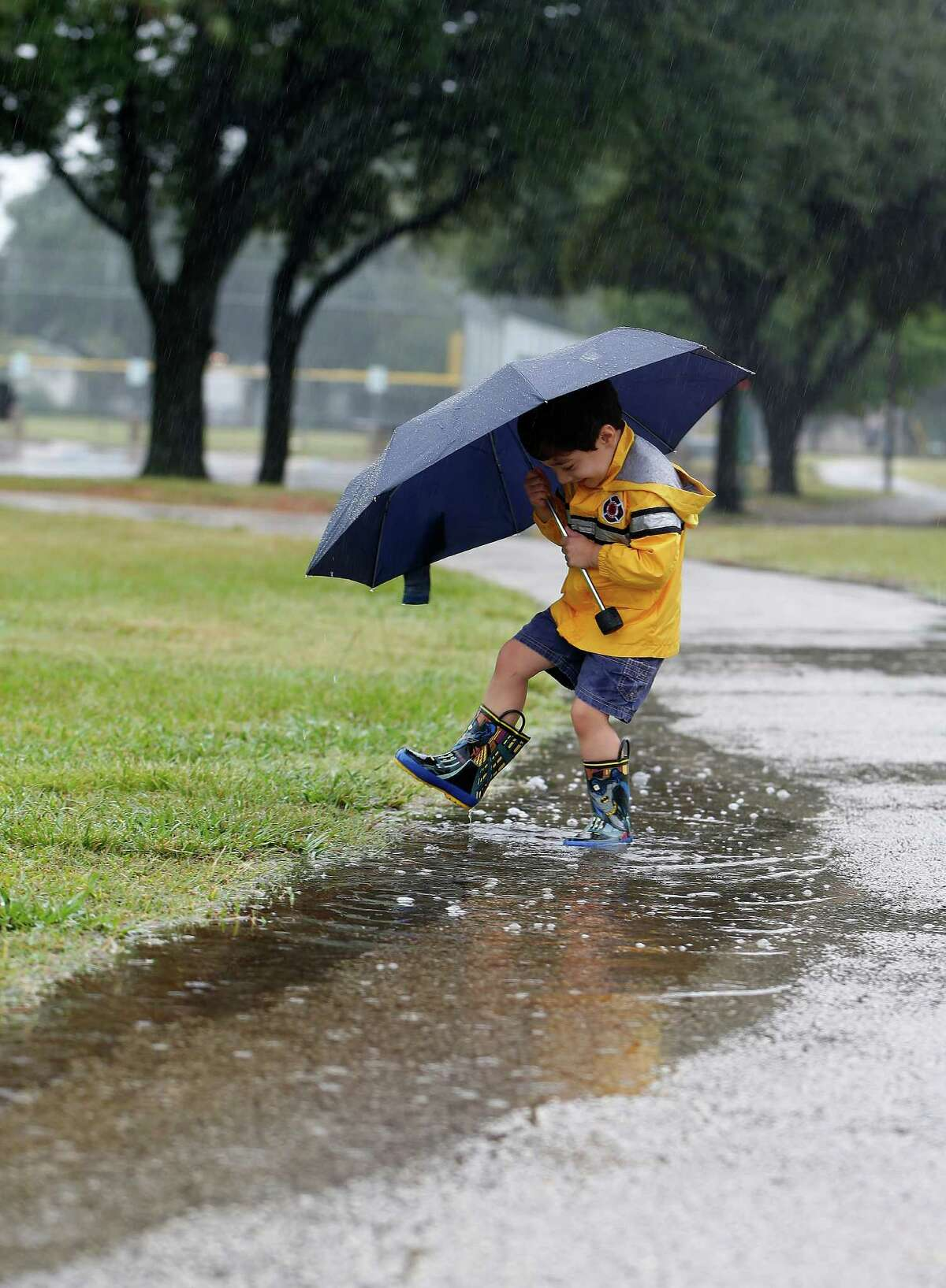 James Yurttas, 3, splashes through puddles Sunday at Stude Park after Hurricane Patricia left almost 10 inches of rain in the Houston area.