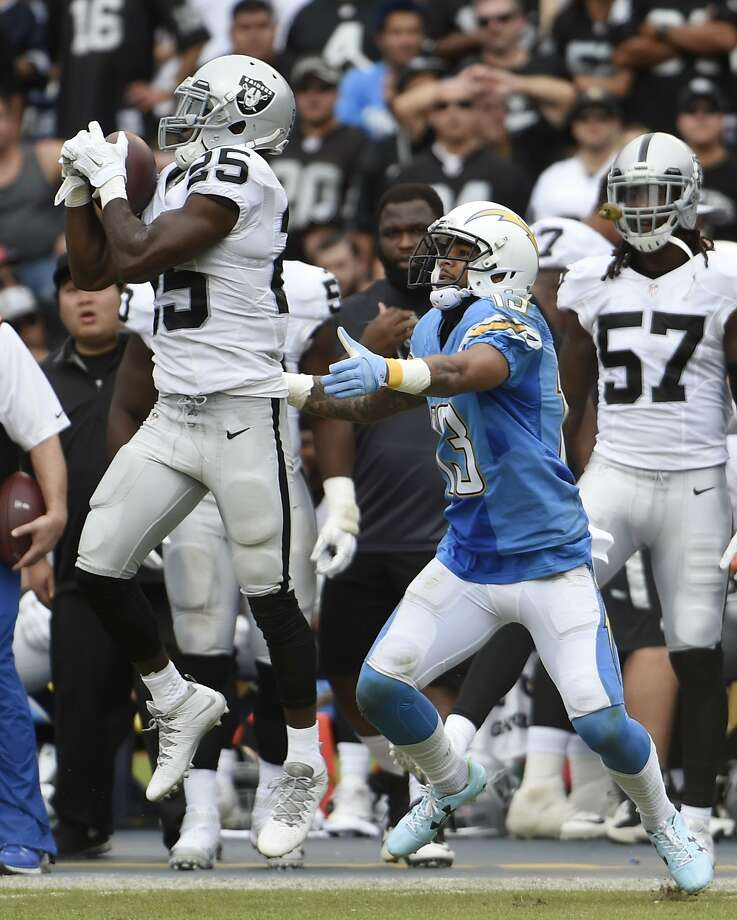 Oakland Raiders cornerback D.J. Hayden makes an interception as San Diego Chargers wide receiver Keenan Allen, right, looks on during the first half of an NFL football game Sunday, Oct. 25, 2015, in San Diego. (AP Photo/Denis Poroy) Photo: Denis Poroy, Associated Press