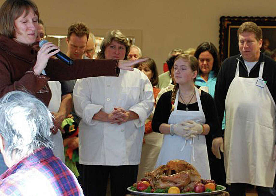 The annual community Thanksgiving feast returns to Saugatuck Congregational Church after being displaced by a fire four years ago. Here, at an earlier gathering, the Rev. Alison Buttrick Patton blesses the bounty provided for the holiday meal. Photo: File Photo / File Photo / Westport News