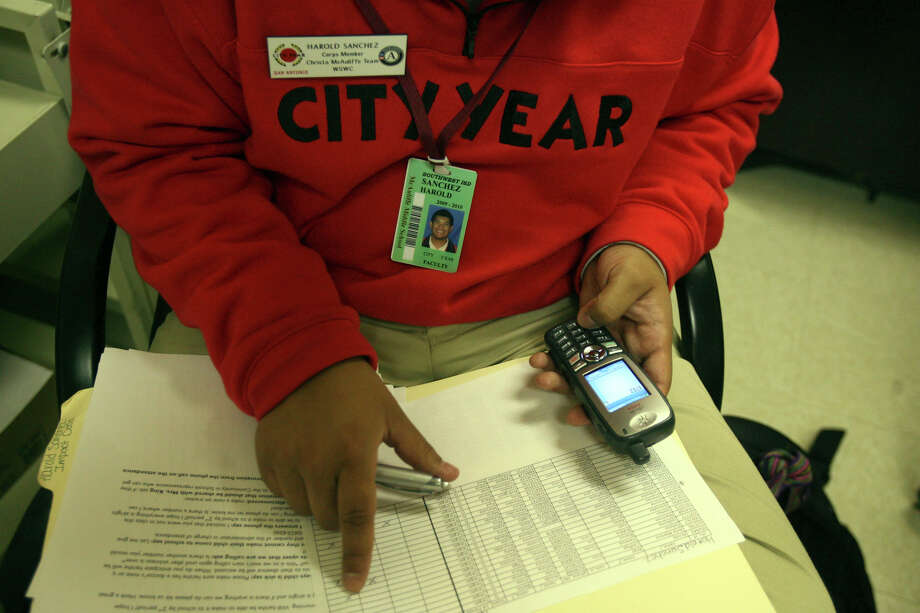 In this file photo, a City Year member goes through a list of absent children at McAuliffe Middle School and makes calls to their homes to check on them. Photo: JOHN DAVENPORT /SAN ANTONIO EXPRESS-NEWS / jdavenport@express-news.net