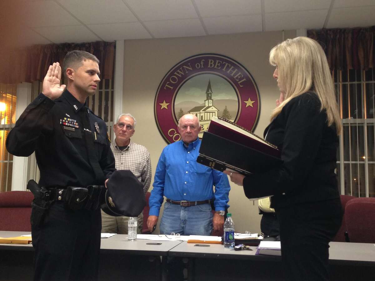 Sgt. James Christos is sworn into his new position with the Bethel Police Department during a ceremony at the municipal center on Wednesday, Oct. 21.