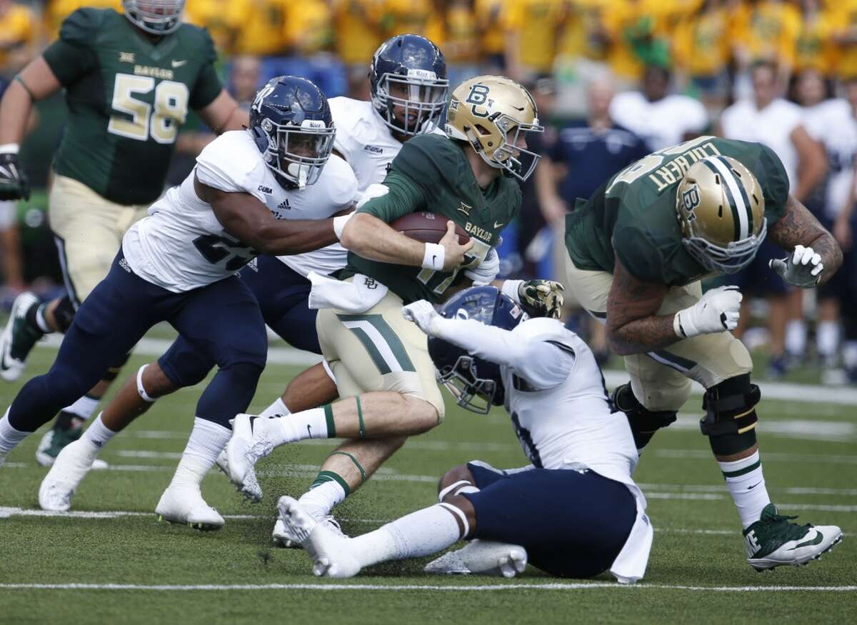 Baylor quarterback Seth Russell (17), center runs against Rice linebacker Tabari McGaskey (25), left,Rice safety JT Ibe (17), right, in the first half of an NCAA college football game, Saturday, Sept. 26, 2015, in Waco, Texas. Blocking for Baylor is Baylor offensive lineman Pat Colbert (69), right. (AP Photo/Rod Aydelotte)