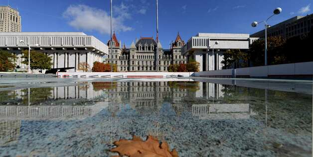 The State Capitol is reflected on the surface of the Empire State Plaza skating rink, which  is being assembled for the season Monday, Oct. 26, 2015, in Albany, N.Y. The rink is scheduled to open December 4, weather permitting. (Will Waldron/Times Union) Photo: Will Waldron / 00033938A