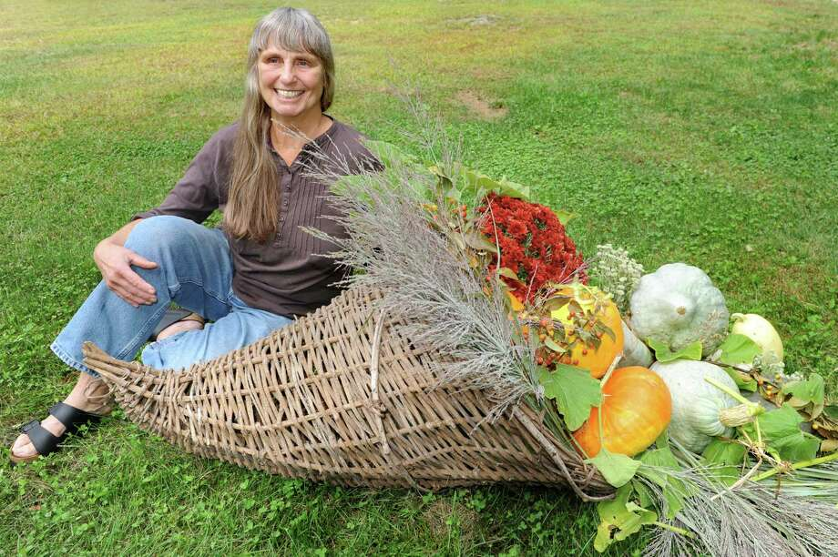 Business owner Barbara Jefts with a cornucopia with full-sized gourdes, squash, pumpkin, mums and ornamental grass on Tuesday, Sept. 22, 2015, at Native Farm Flowers in Greenfield Center, N.Y. (Cindy Schultz / Times Union) Photo: Cindy Schultz / 00033412A