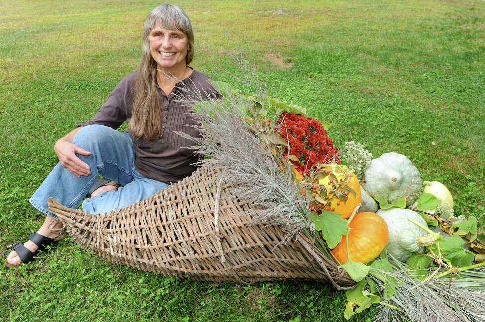 Business owner Barbara Jefts with a cornucopia with full-sized gourdes, squash, pumpkin, mums and ornamental grass on Tuesday, Sept. 22, 2015, at Native Farm Flowers in Greenfield Center, N.Y. (Cindy Schultz / Times Union)