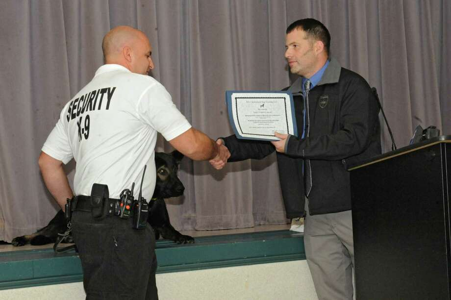 Handler Rick Rhodes, left, accepts a certificate of training from Michael D'Abruzzo, head of the Paladin training academy, at Ellis Hospital on Monday, Oct. 26, 2015 in Schenectady, N.Y. Ellis Medicine's security newest team member Cargo, a K-9 dog, will work to help reduce security incidents, especially in the Emergency Department, where tensions can run high. (Lori Van Buren / Times Union) Photo: Lori Van Buren / 10033913A