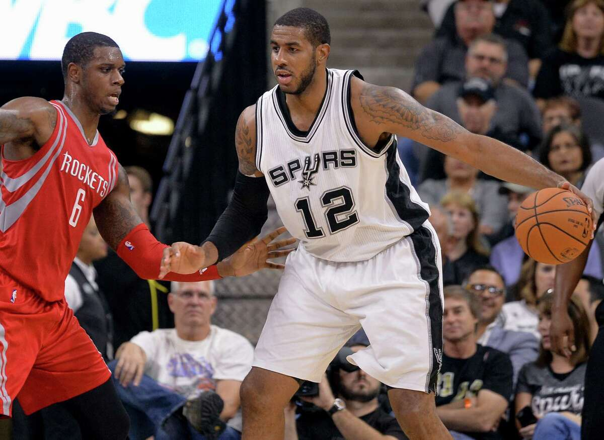 Spurs forward LaMarcus Aldridge (12) is defended by Houston Rockets forward Terrence Jones during the first half of a preseason NBA basketball game, Friday, Oct. 23, 2015, in San Antonio.