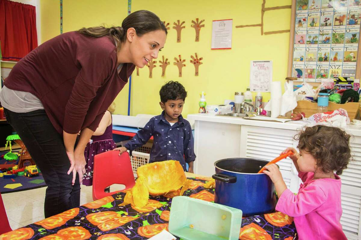 Union Memorial Preschool head teacher Emily Benett talks with children as they work on a Halloween activity. The school announced it will now take in 2-year-olds.
