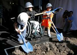 Mats O'Brian (left), 5, Genuine Rivas, 6, and Amro Housheya shovel dirt at a groundbreaking ceremony for the UCSF Benioff Children's Hospital in Oakland, California, on Monday, Oct. 26, 2015.