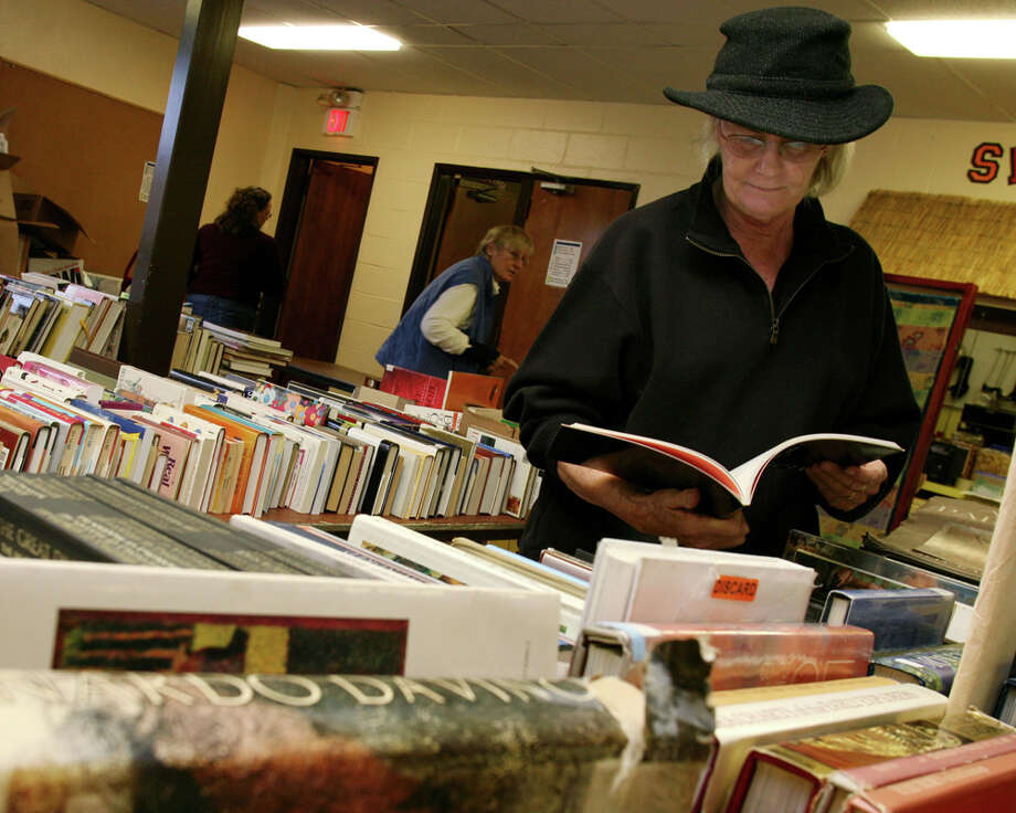 Candy Le Guay, of Sydney Australia, gets an early look at some of the books for sale at the Friends of the Byram Shubert Library's book and media sale in 2011. This year's sale starts Nov. 6. Photo: David Ames / David Ames / Greenwich Time