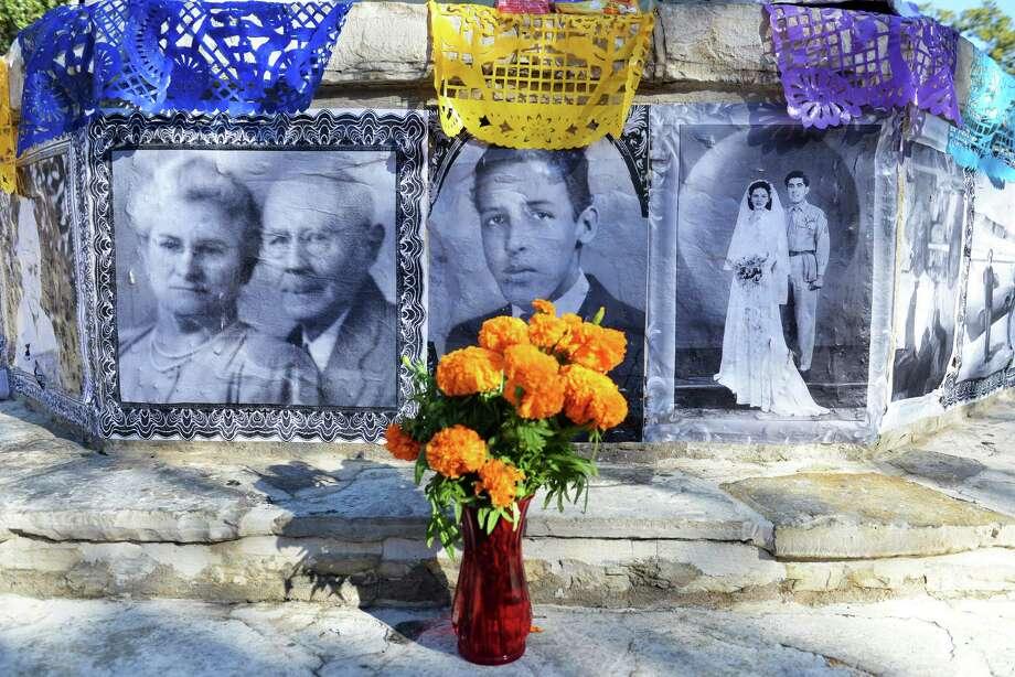 Photographs of deceased family members surround the main fountain at La Villita on Dia de Los Muertos in San Antonio on Saturday, Nov. 1, 2014. Family members placed the photographs around the fountain to remember them on this day. Photo: Matthew Busch, Freelancer / © San Antonio Express-News