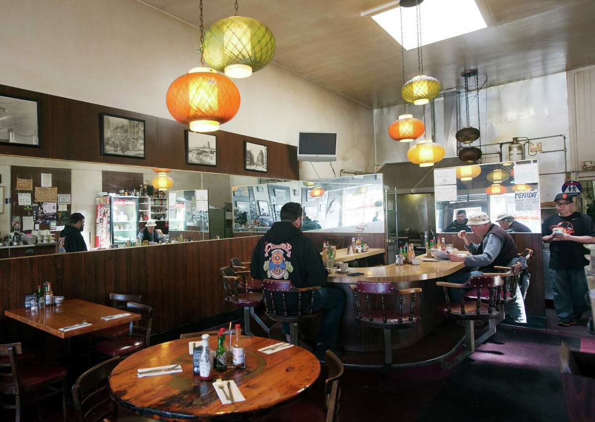 The interior of the Howard's Cafe in San Francisco had original light fixtures from when the cafe opened and a round counter to eat in the back.