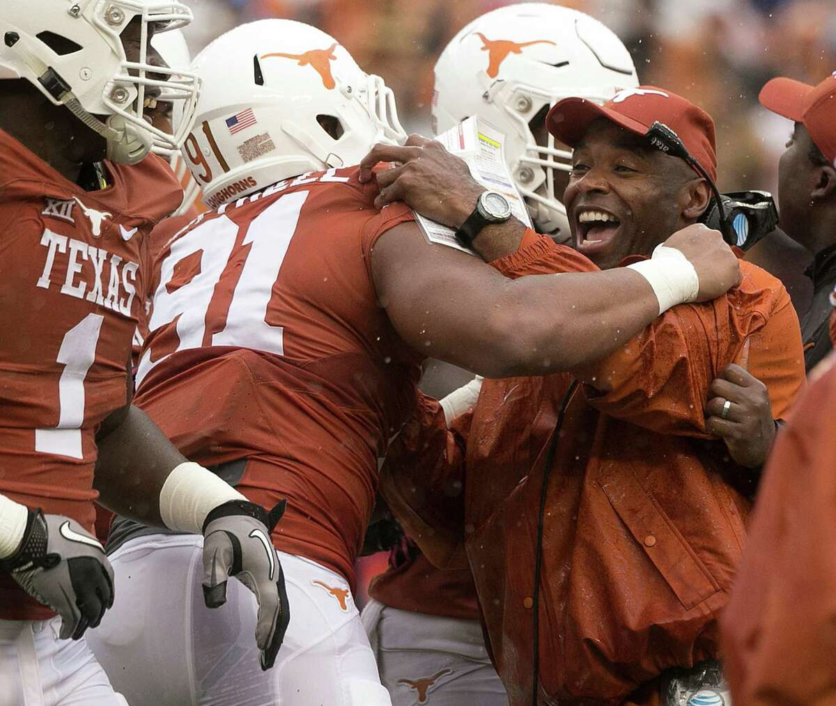 Texas head coach Charlie Strong celebrates with Bryce Cottrell (91) after a sack of Kansas State quarterback in the fourth quarter at Royal Memorial Stadium in Austin, Texas, on Saturday, Oct. 24, 2015. Texas won, 23-9. (Deborah Cannon/American-Statesman/TNS)