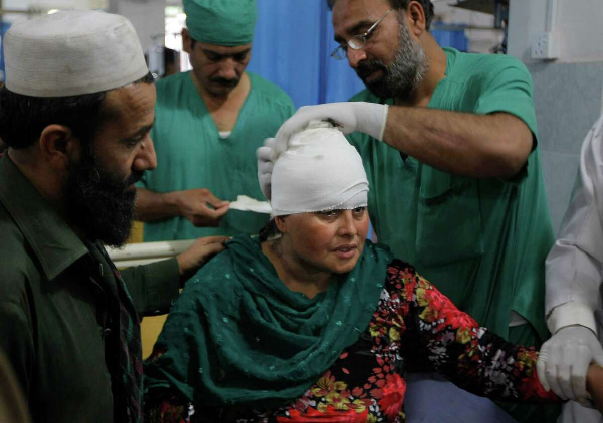 Doctors at a hospital in Peshawar, Pakistan, treat a woman who was injured in the earthquake.