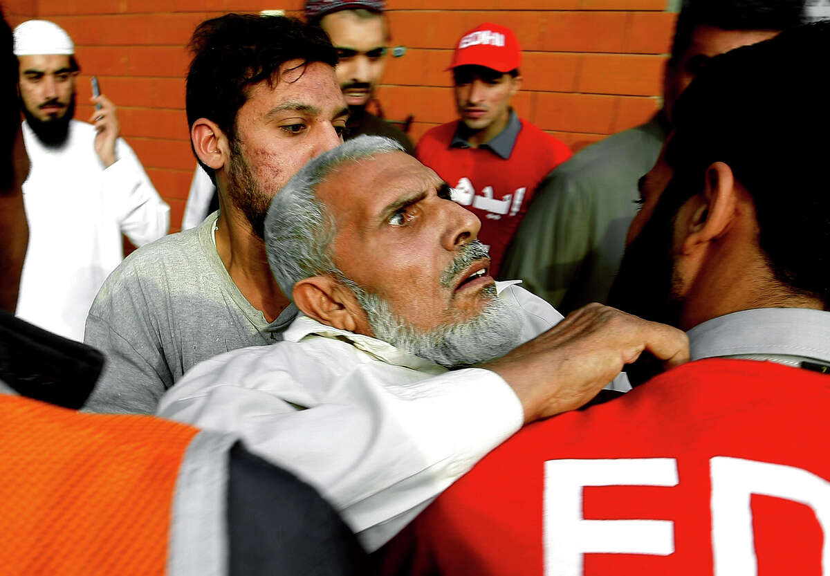 Pakistani rescue workers carry a man traumatized by the earthquake to a hospital in Peshawar, Pakistan.