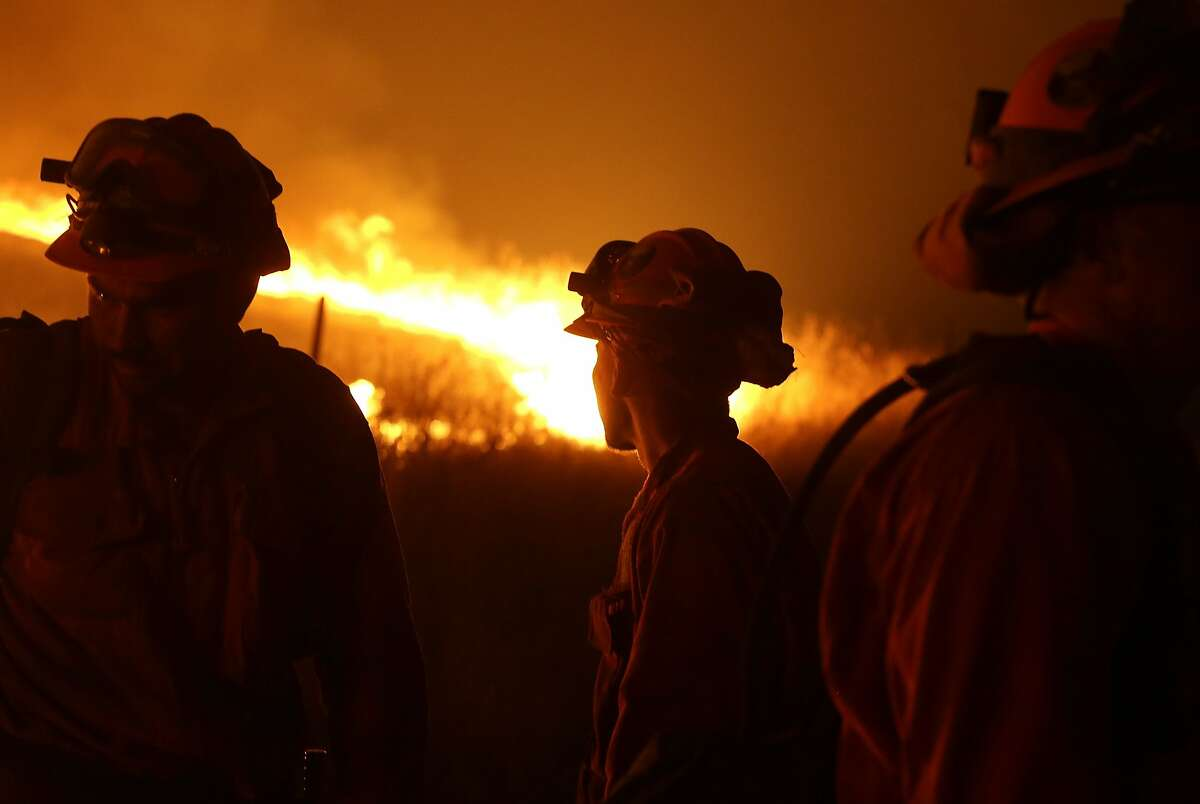 California Department of Corrections and Rehabilitation inmates stand guard as flames from the Butte Fire approach a containment line Saturday, Sept. 12, 2015 near San Andreas, Calif.(AP Photo/Rich Pedroncelli)