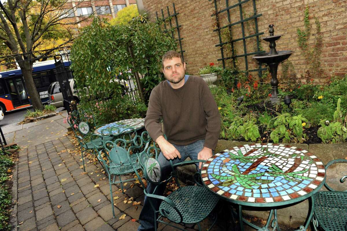 Owner Kevin Dively sits in the cafe's courtyard along Washington Avenue on Wednesday, Oct. 21, 2015, at the Iron Gate Cafe in Albany, N.Y. (Cindy Schultz / Times Union)
