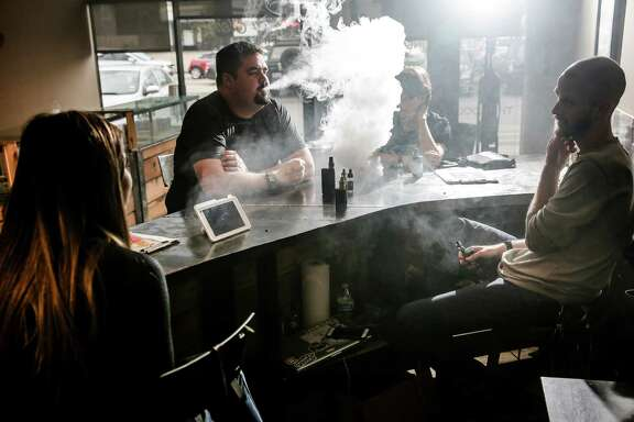 Alex Perez-Guerra, center, vapes at New Element Fine Vapors with employee Melissa Torres, left, and owner Daniel Adell, right, Monday, Oct. 26, 2015, in Houston.