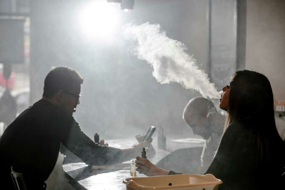 FILE - New Element Fine Vapors employee Melissa Torres, right, vapes with Nate Pingor, left, and owner Daniel Adell in the shop Oct. 26, 2015, in Houston, Texas. Photo: Michael Ciaglo, Houston Chronicle / © 2015 Houston Chronicle