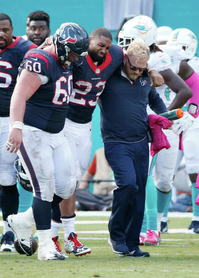 Houston Texans running back Arian Foster is helped off the field by center Ben Jones and an unidentified team training member during the second half of against the Miami Dolphins. Photo: Wilfredo Lee /Associated Press / AP