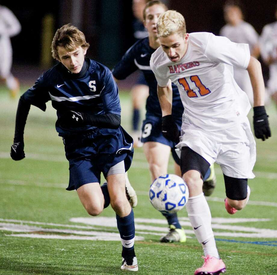 Staples High School's Daniel Reid and Danbury High School's Kevin Spennato chase the ball in a game played at Danbury. Monday, Oct. 26, 2015 Photo: Scott Mullin / For The / The News-Times Freelance
