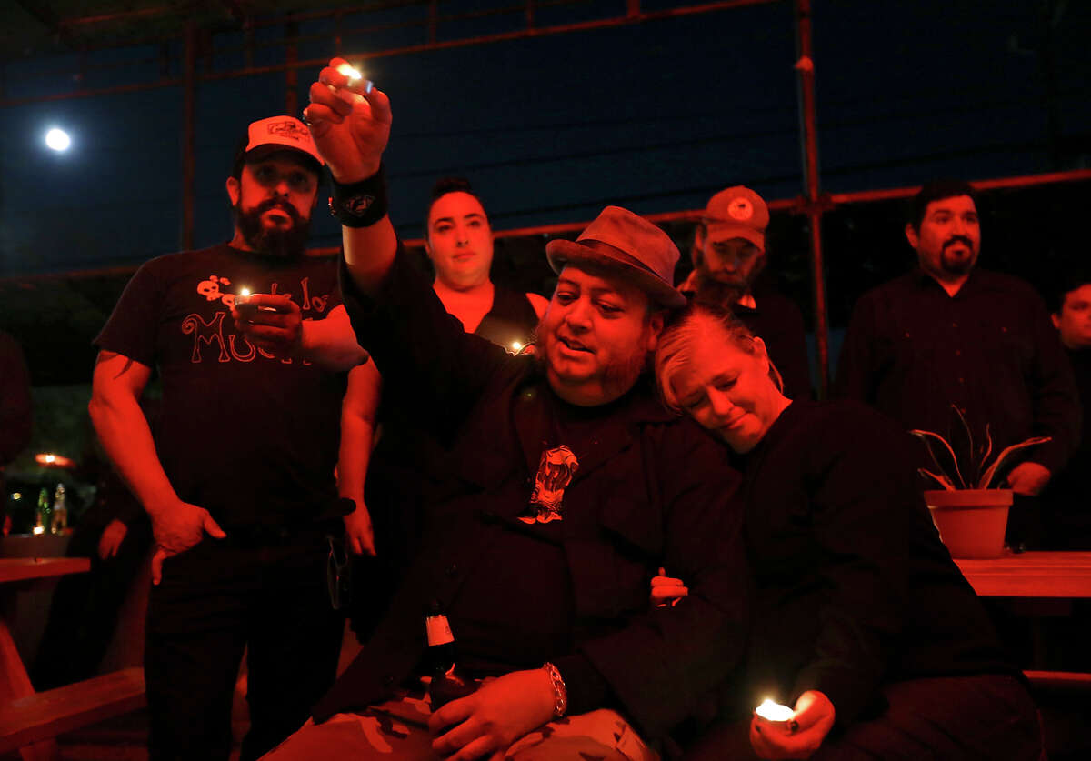Paul Lopez (center left), his fiancŽe Adrianna Collins, and others attend a memorial, at La Botanica Monday Oct. 26, 2015, for friend musician Shawn Terry, a fixture on the St. Mary's Strip with such bands as the Mechanical Walking Robotboy and Guilty Strangers. Terry died on Saturday from complications of cancer after being diagnosed in the fall.
