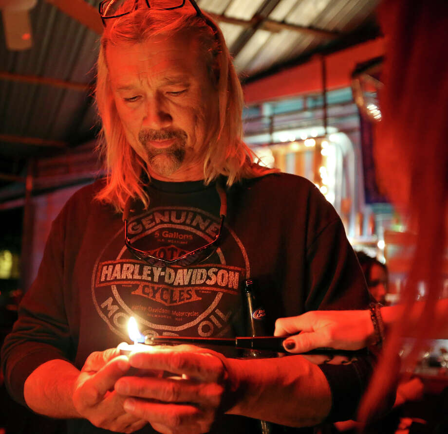 "Andrea Mota (right) lights Ron ""Hondo"" Horecka candle , during a memorial, at La Botanica Monday Oct. 26, 2015, for musician Shawn Terry, a fixture on the St. Mary's Strip with such bands as the Mechanical Walking Robotboy and Guilty Strangers. Shawn Terry died on Saturday from complications of cancer after being diagnosed in the fall. Photo: Edward A. Ornelas, San Antonio Express-News / © 2015 San Antonio Express-News"
