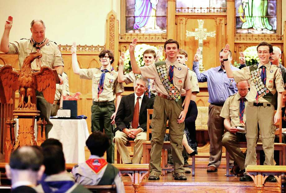 At a recent Eagle Court of Honor hosted by Boy Scout Troop 100, new Eagle Scouts Gregory Hellman, center stage, and Wellington Baumann, right, join Assistant Scoutmaster Kurt Fenstermacher in leading the gathering in the Eagle Oath and Charge at Christ & Holy Trinity Church. Photo: Contributed / Contributed Photo / Westport News