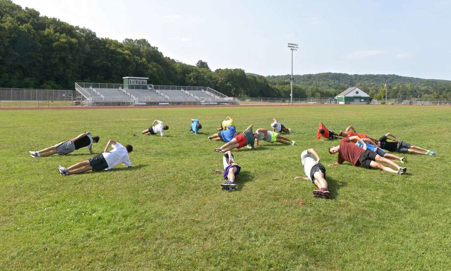 The New Milford High School cross county team works out on the main athletic field of the high school. This field and a second at the school will receive artificial turf, with the track upgraded and lighting installed. Photo: H John Voorhees III / Hearst Connecticut Media / The News-Times