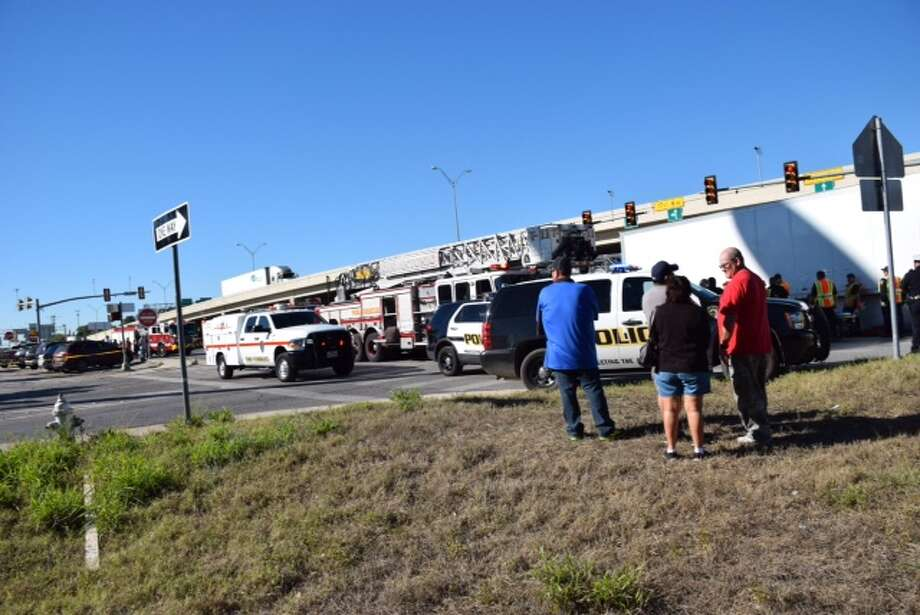 San Antonio emergency crews work to cut a man from a car that became pinned under an 18-wheeler's trailer on the Interstate 35 access road on the South Side on Oct. 27, 2015. Photo: By Mark D. Wilson/San Antonio Express-News