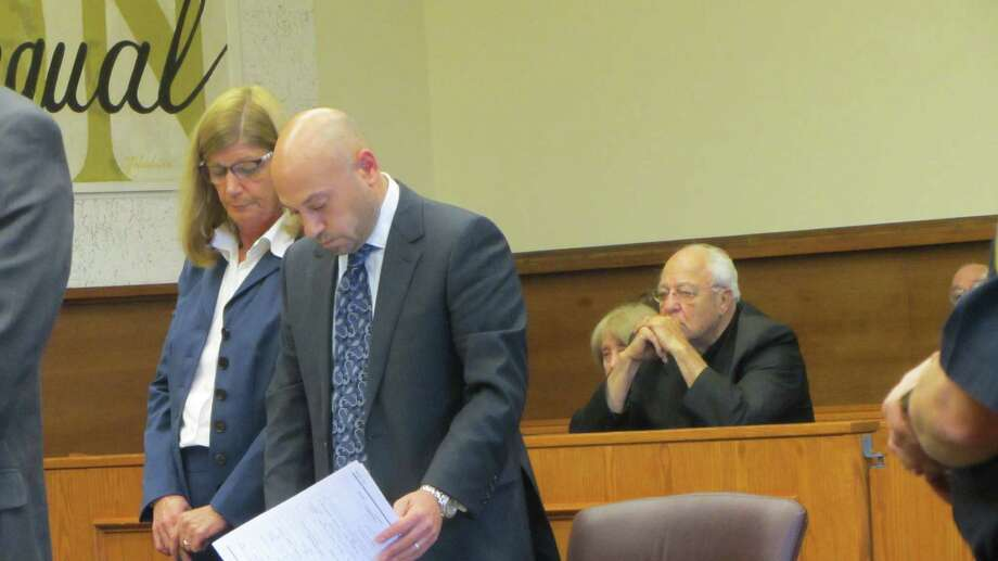 Jacquelyn Gentile, left, and her attorney, Andrew Safranko, wait for the judge to impose sentence. Behind them sits the Rev. Peter Young sits with his hands to his face. (Bob Gardinier / Times Union)