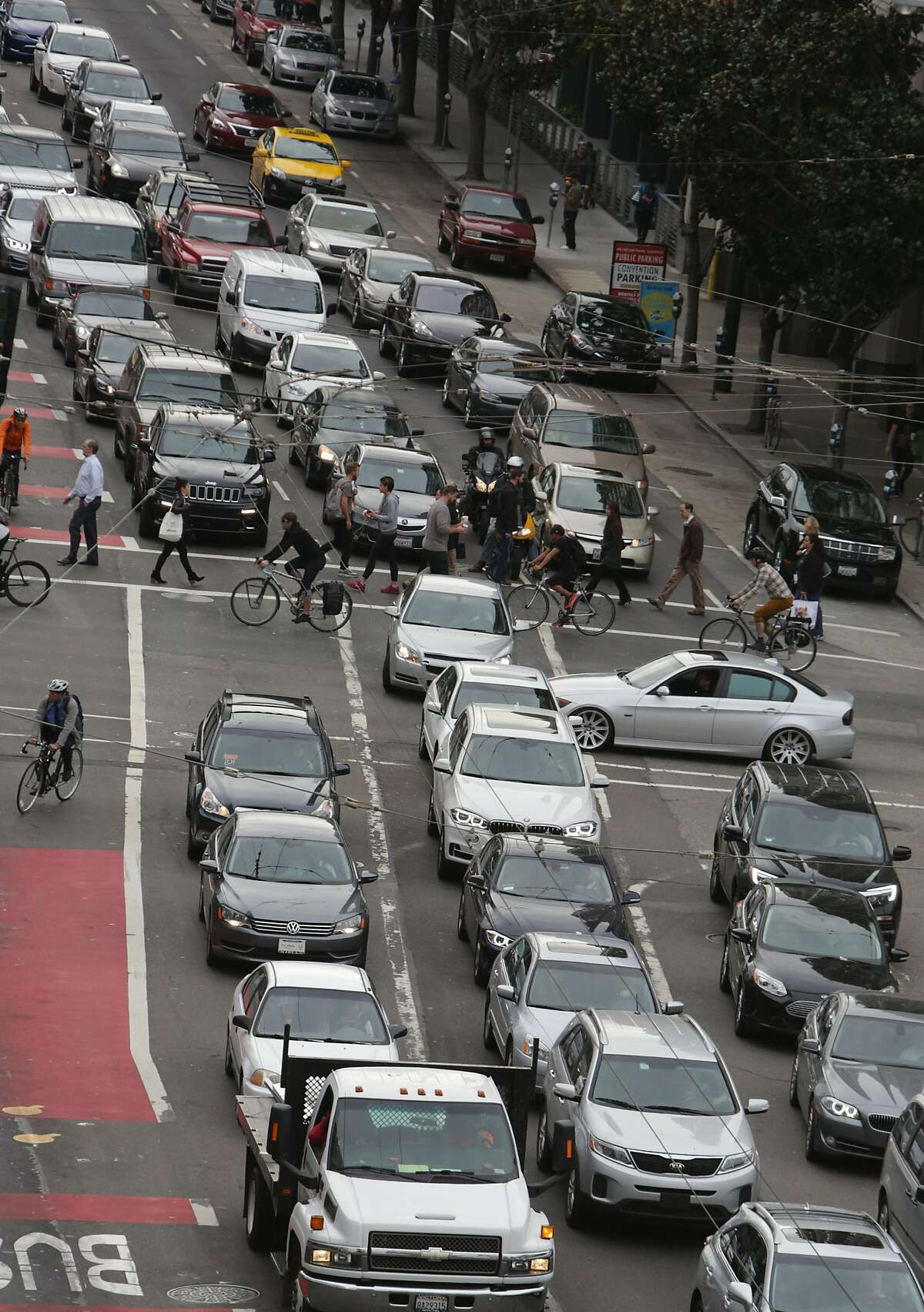 Vehicles sit in traffic along Third Street as bicyclists, pedestrians and vehicles on Folsom Street cross and turn onto Third Street on Tuesday, October 27, 2015 in San Francisco, Calif.