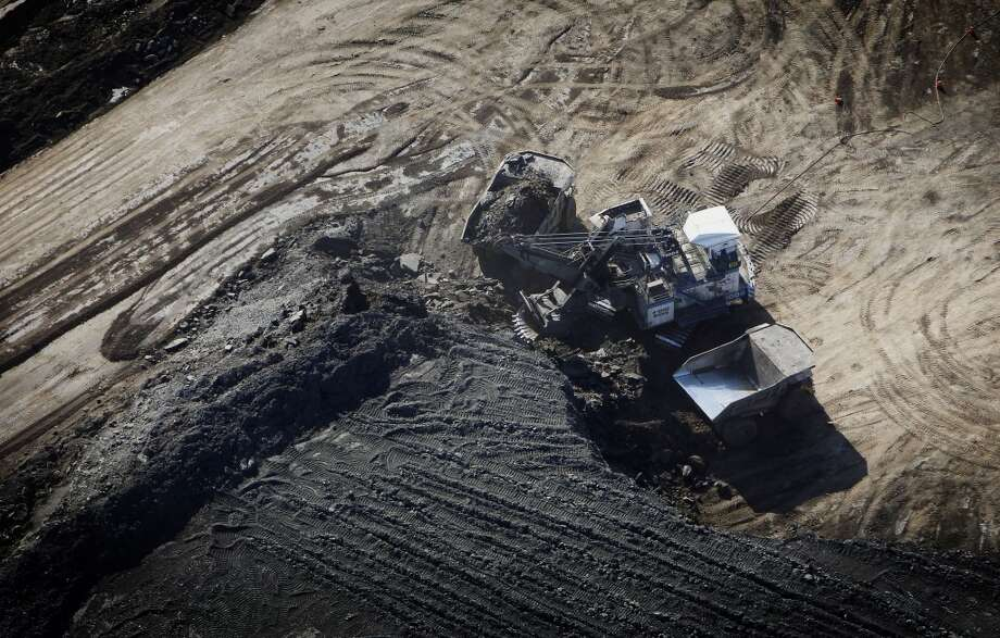 A dump truck is loaded with oil sands at the Suncor Energy Inc. mine in this aerial photograph taken near Fort McMurray, Alberta, Canada, on Thursday, June 4, 2015. Photographer: Ben Nelms/Bloomberg Photo: Ben Nelms, Bloomberg